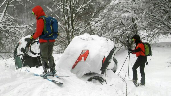 Members of Lazio's Alpine and Speleological Rescue Team are seen next to cars covered in snow in front of the Hotel Rigopiano in Farindola, central Italy, hit by an avalanche, in this January 19, 2017 handout picture provided by Lazio's Alpine and Speleological Rescue Team - Sputnik International