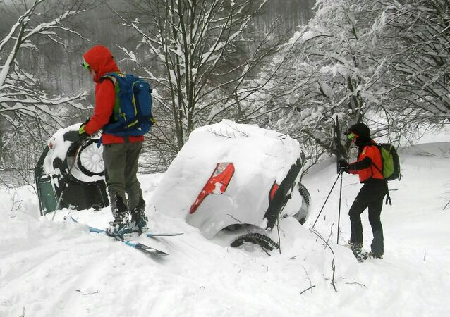 Members of Lazio's Alpine and Speleological Rescue Team are seen next to cars covered in snow in front of the Hotel Rigopiano in Farindola, central Italy, hit by an avalanche, in this January 19, 2017 handout picture provided by Lazio's Alpine and Speleological Rescue Team
