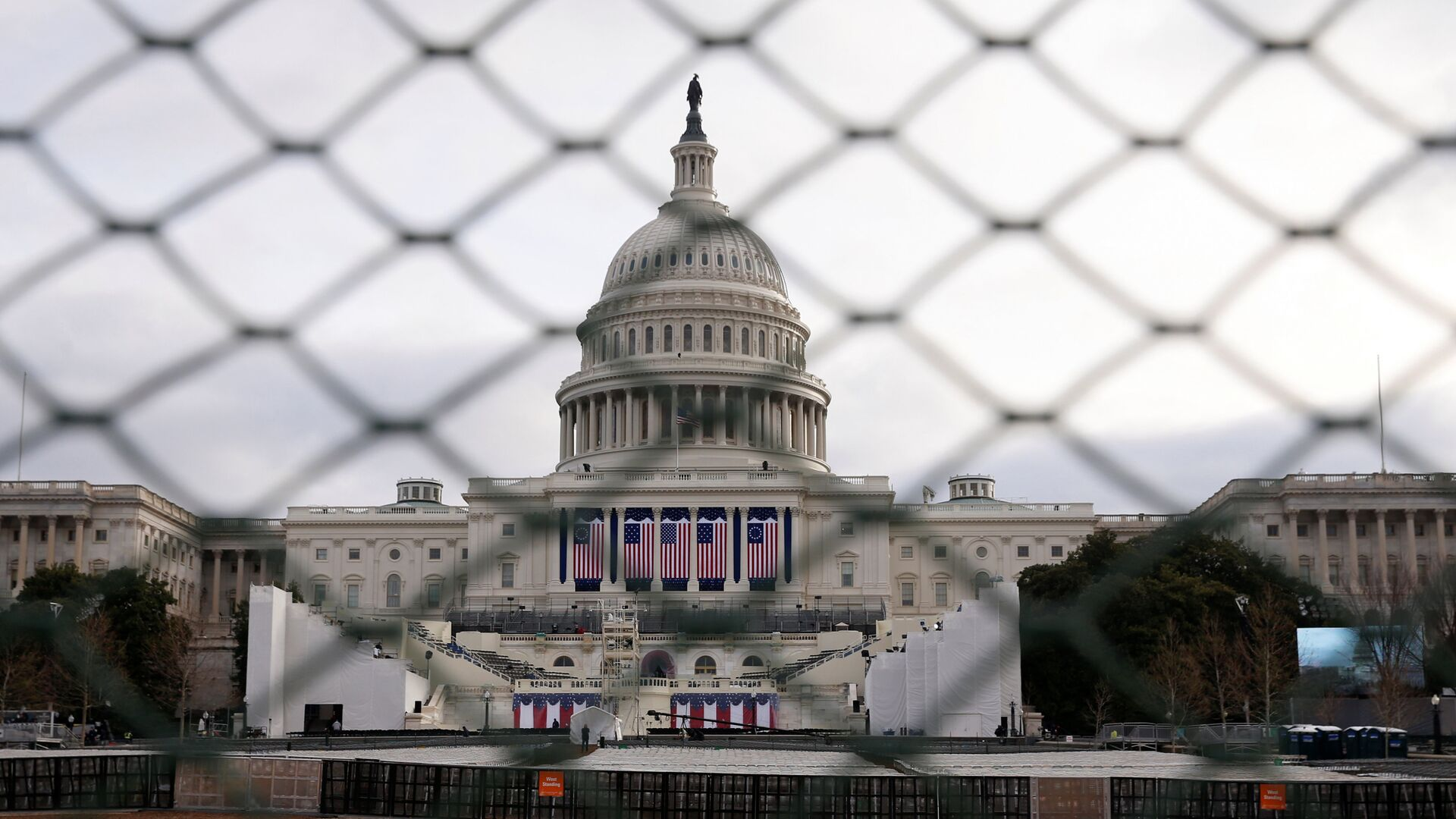 The U.S. Capitol building is seen behind a security fence in Washington ahead of the 2017 Presidential Inauguation. - Sputnik International, 1920, 12.09.2021