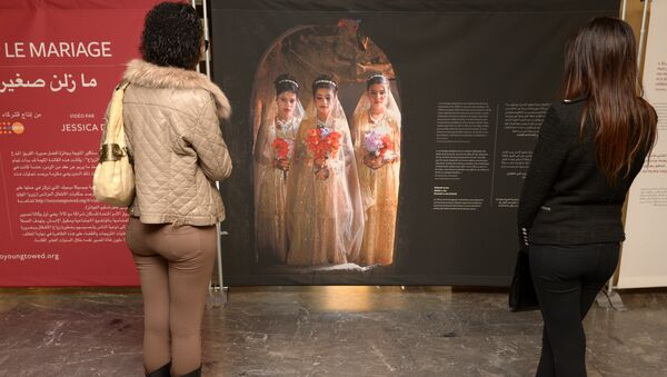 Moroccan women look at photographs of under-age brides during an exhibition by Stephanie Sinclair at the Mohammed V theatre in Rabat on December 4, 2013 - Sputnik International