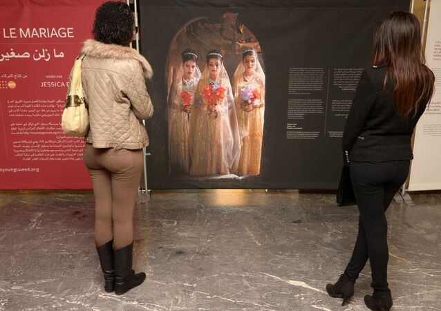 Moroccan women look at photographs of under-age brides during an exhibition by Stephanie Sinclair at the Mohammed V theatre in Rabat on December 4, 2013