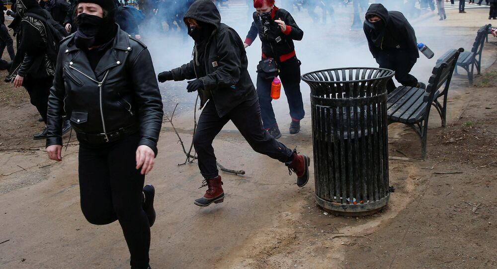 Activists race after being hit by a stun grenade while protesting against U.S. President-elect Donald Trump on the sidelines of the inauguration in Washington, U.S., January 20, 2017.