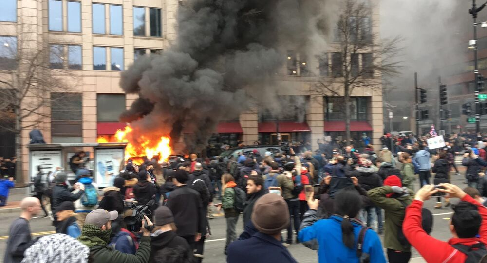 A car set aflame by anti-Trump protesters.