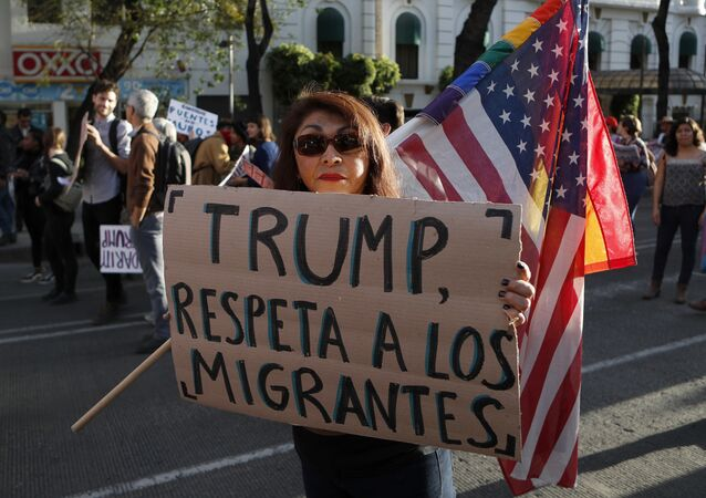 A woman holds a sign that reads in Spanish Trump, respect migrants during a march called by a local women's movement against U.S. President Donald Trump in Mexico City, Friday, Jan. 20, 2017