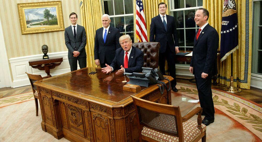 U.S. President Donald Trump, flanked by Senior Advisor Jared Kushner (standing, L-R), Vice President Mike Pence, Staff Secretary Rob Porter and Chief of Staff Reince Priebus, welcomes reporters into the Oval Office for him to sign his first executive orders at the White House in Washington, U.S. January 20, 2017
