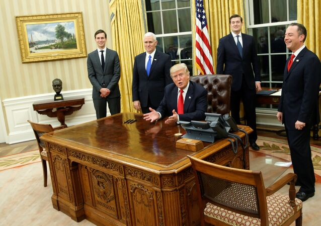 US President Donald Trump, flanked by Senior Advisor Jared Kushner (standing, L-R), Vice President Mike Pence, Staff Secretary Rob Porter and Chief of Staff Reince Priebus, welcomes reporters into the Oval Office for him to sign his first executive orders at the White House in Washington, U.S. January 20, 2017
