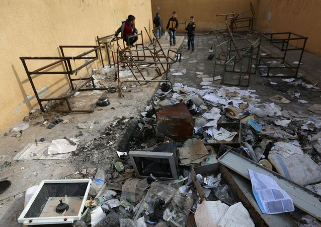 Students stand amid damaged desks and books in 'Aisha Mother of the BelieversÕ school which was recently reopened after rebels took control of al-Rai town from Islamic State militants, Syria January 17, 2017