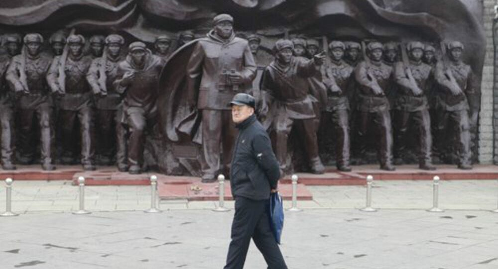 An old man walks in front of a statue of the People's Volunteer Army near the Dandong Broken Bridge Scenic Area