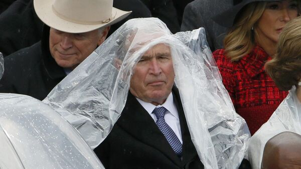 Former president George W. Bush keeps covered in the rain as he sits with his wife Laura at the inauguration ceremonies swearing in Donald Trump as the 45th president of the United States on the West front of the U.S. Capitol in Washington, U.S., January 20, 2017 - Sputnik International