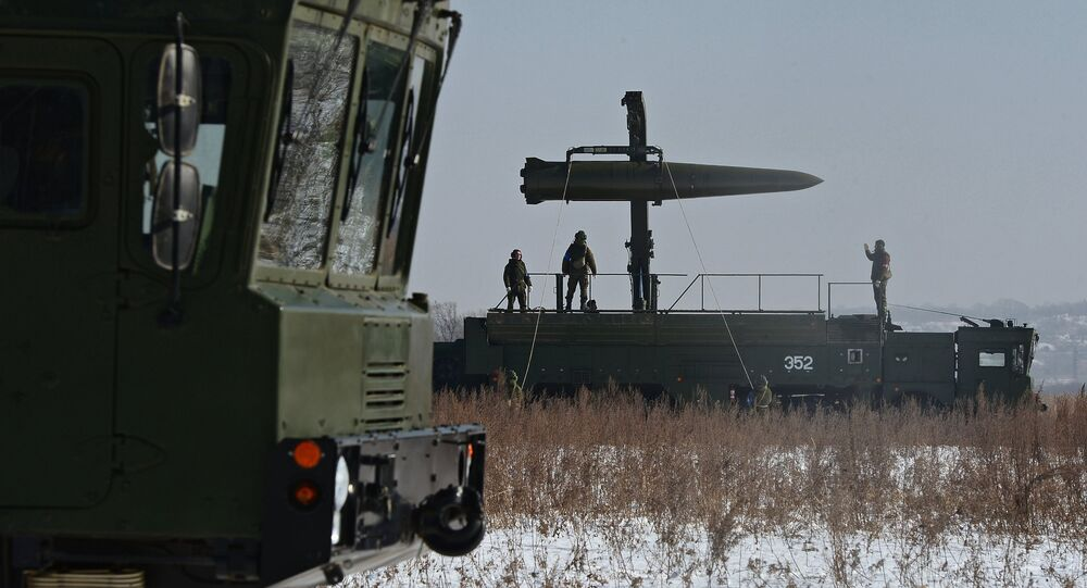 Russian soldiers watch a transporter-loader place an Iskander-M shorter-range missile onto a self-propelled launcher