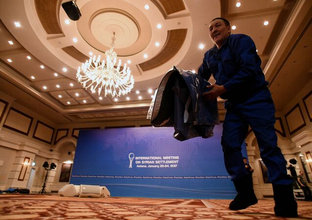 A picture taken on January 22, 2017 shows a man at work to prepare the Syria peace talks conference room at Astana' Rixos President Hotel