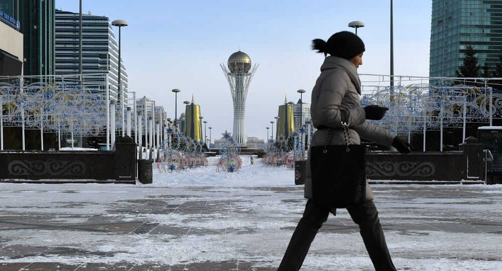 A picture taken on January 22, 2017 shows a woman walking in downtown Astana, with the Baiterek monument seen in the background