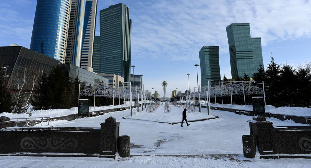 A picture taken on January 22, 2017 shows a man walking in downtown Astana, with the Baiterek monument seen in the background