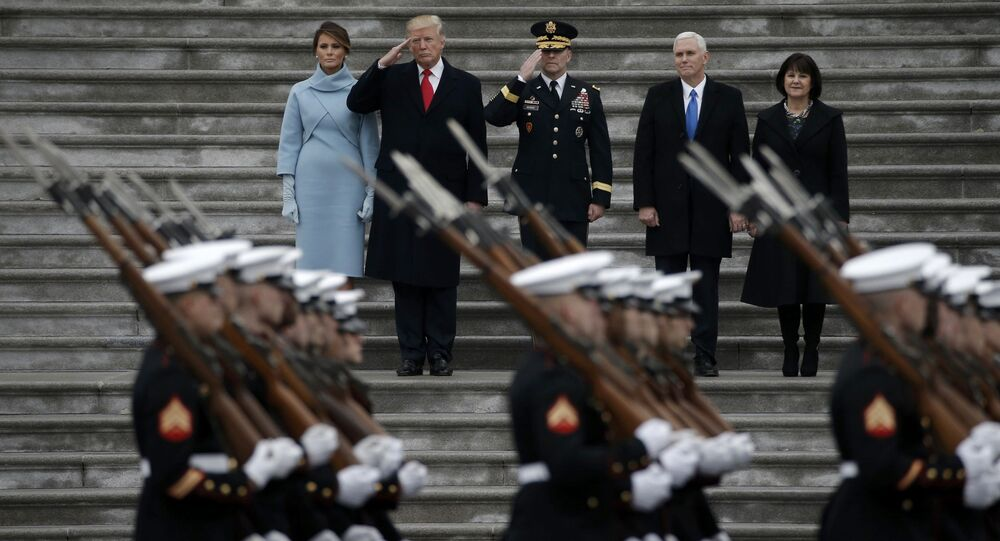 Newly inaugurated U.S. President Donald Trump (in red tie), first lady Melania (L), Vice President Mike Pence and his wife Karen (R) preside over a military parade during Trump's swearing ceremony in Washington, U.S., January 20, 2017