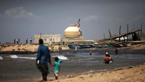 A fisherman and his son stand near the Russian-built Kudankulam Atomic Power Project, at Kudankulam, about 700 kilometers (440 miles) south of Chennai, Tamil Nadu state, India, Thursday, Sept. 13, 2012 - Sputnik International