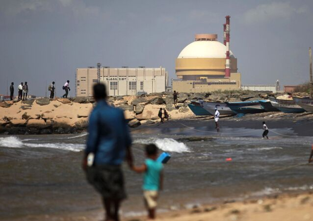 A fisherman and his son stand near the Russian-built Kudankulam Atomic Power Project, at Kudankulam, about 700 kilometers (440 miles) south of Chennai, Tamil Nadu state, India, Thursday, Sept. 13, 2012