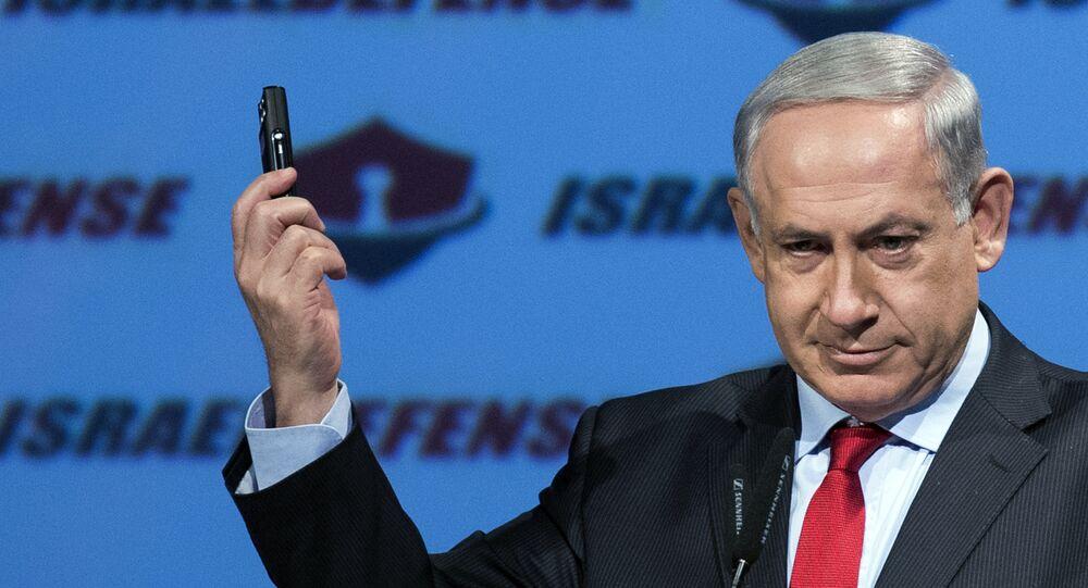 Israeli Prime Minister Benjamin Netanyahu shows a mobile phone (File)