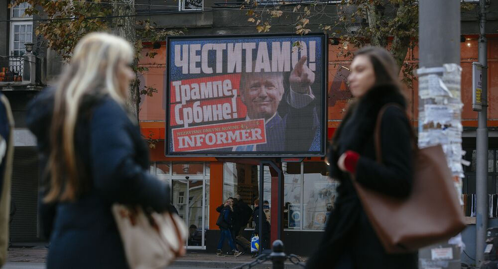 Pedestrians walk by a billboard picturing US President-elect Donald Trump with an inscrpition that translates as Congratulations! Trump, Serb! published by Serbian daily newspaper in Belgrade on November 10, 2016