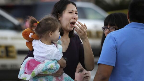 A woman holds her child after San Antonio police helped her and other shoppers exit the Rolling Oaks Mall, Sunday, Jan. 22, 2017, in San Antonio, after a deadly shooting. Authorities say several were injured after a robbery at the shopping mall. - Sputnik International