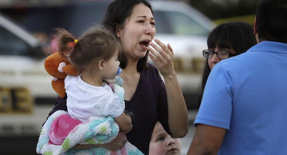 A woman holds her child after San Antonio police helped her and other shoppers exit the Rolling Oaks Mall, Sunday, Jan. 22, 2017, in San Antonio, after a deadly shooting. Authorities say several were injured after a robbery at the shopping mall.