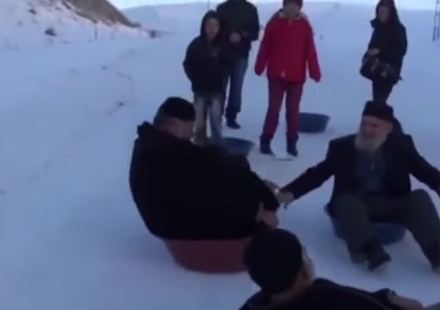 Rolling back the years: Grandpas slide down snowy slope