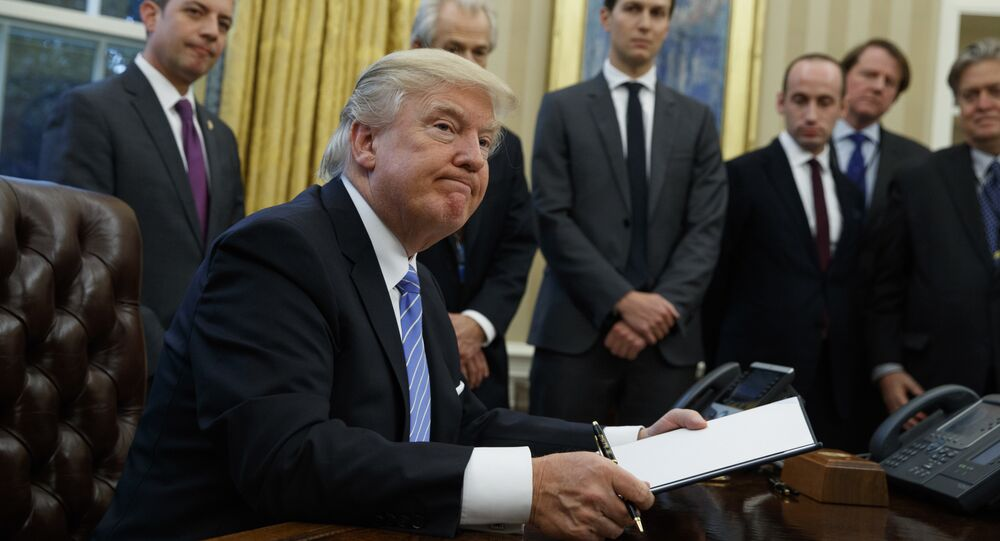 President Donald Trump looks up after signing the final of three executive orders, Monday, Jan. 23, 2017, in the Oval Office of the White House in Washington. (AP Photo/Evan Vucci)