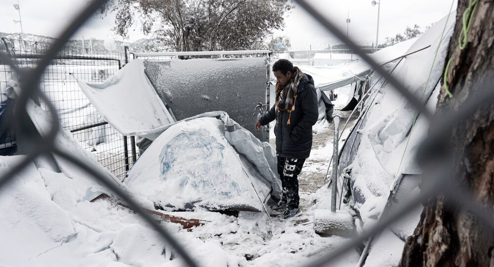 A migrant stands next to a snow-covered tent at the Moria hotspot on the island of Lesbos , following heavy snowfalls on January 7, 2017.