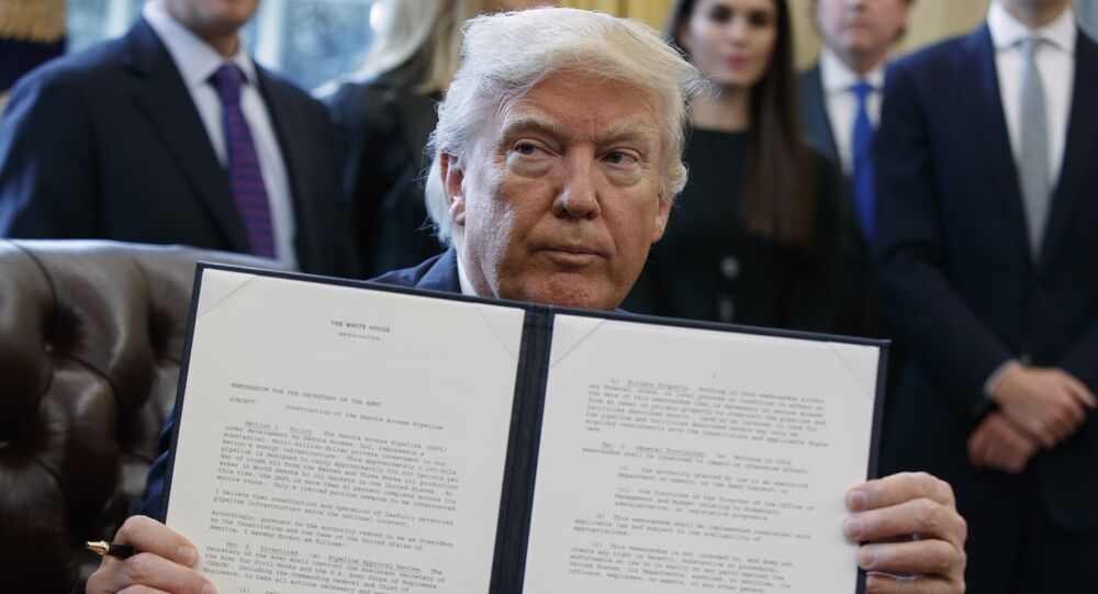President Donald Trump shows off his signature on an executive order about the Dakota Access pipeline in the Oval Office of the White House in Washington