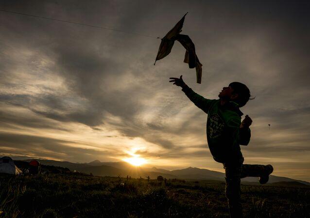 A refugie boy flies his kite at sunset