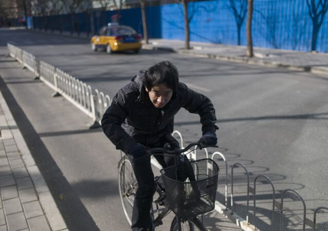 A man rides his bike in the street in Beijing (file)