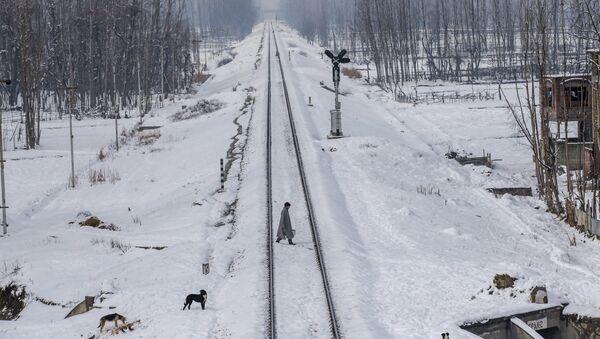 A Kashmiri man crosses snow covered railway track in the outskirts of Srinagar, Indian controlled Kashmir - Sputnik International