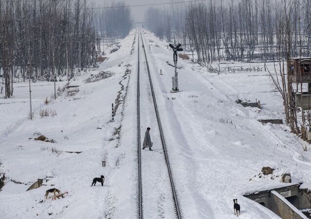 A Kashmiri man crosses snow covered railway track in the outskirts of Srinagar, Indian controlled Kashmir