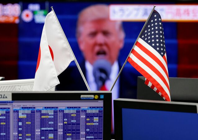 National flags of Japan and the U.S. are seen in front of a monitor showing U.S. President Donald Trump at a foreign exchange trading company in Tokyo, Japan, January 23, 2017