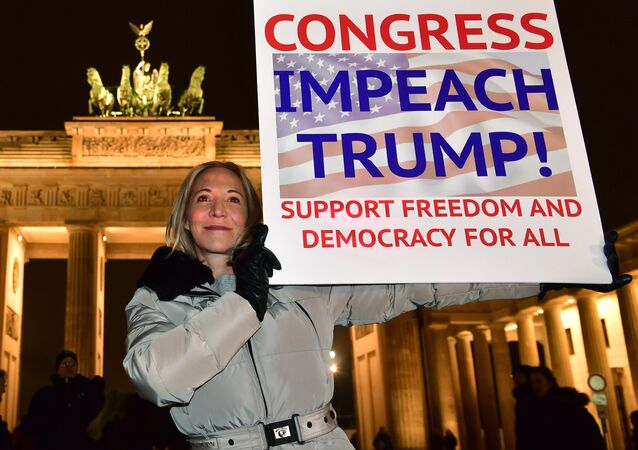 A protester shows a banner during an anti Donald Trump rally, on the day of his inauguration as US President, in front of Brandenburg Gate on January 20, 2017 in Berlin
