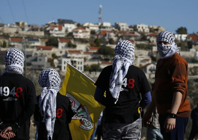 Palestinian protestors stand facing the Israeli settlement of Qadumim (Kedumim) during clashes with Israeli security forces following a demonstration against the expropriation of Palestinian land by Israel in the village of Kfar Qaddum, near Nablus, in the occupied West Bank on December 30, 2016