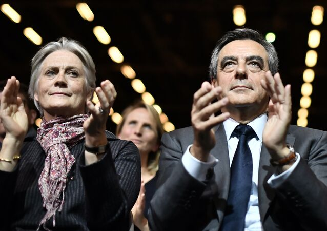 (FILES) This file photo taken on November 25, 2016 shows Francois Fillon (C), candidate for the right-wing primaries ahead of the French 2017 presidential election, and his wife Penelope (L) attending a campaign rally in Paris, ahead of the primary's second round on November 27