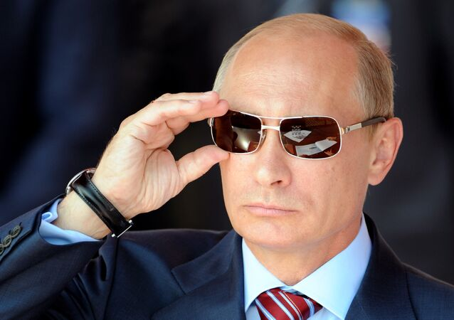 Russian Prime Minister Vladimir Putin adjusts his sunglasses as he watches an air show during MAKS-2011, the International Aviation and Space Show, in Zhukovsky, outside Moscow, on August 17, 2011