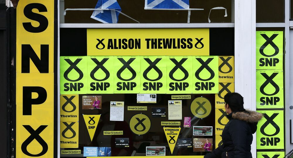 A member of the public walks past a window display of Scottish National Party branding is displayed in Glasgow, Scotland, Thursday, May 7, 2015
