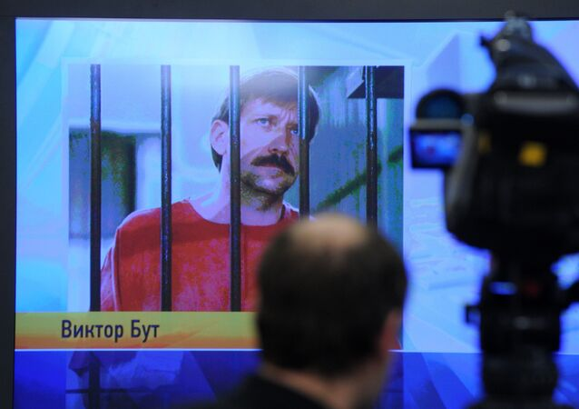 A journalist stands near a screen displaying convicted Russian arms smuggler Viktor Bout in Moscow during a teleconference with Bout from his US prison