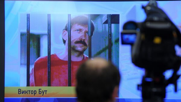A journalist stands near a screen displaying convicted Russian arms smuggler Viktor Bout in Moscow, on 12 April 2012, during a teleconference with Bout from his US prison - Sputnik International