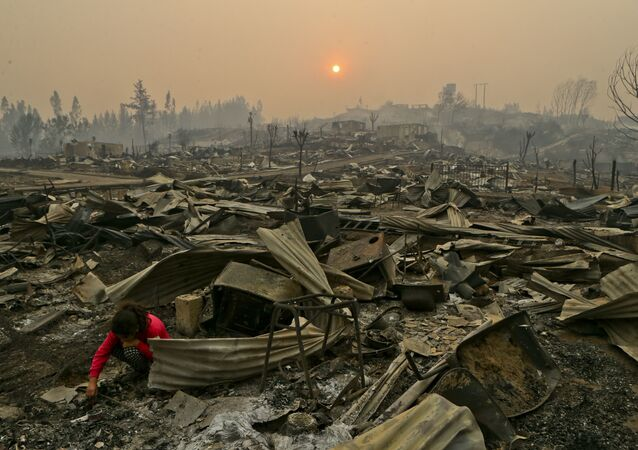A young girl searches the wreckage of what was once her home in the fire-ravaged town of Santa Olga, Chile.