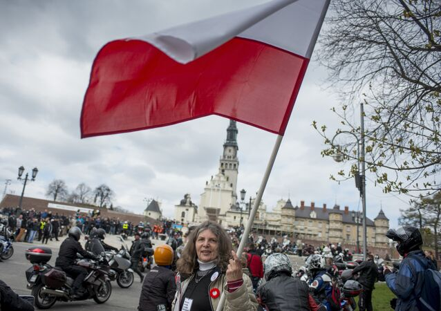 A woman waves a Polish flag in front of the Jasna Gora monastery during the annual Polish motorcyclists pilgrimage to the country's greatest place of pilgrimage hosting the Black Madonna of Czestochowa in Czestochowa, Poland, on April 19, 2015