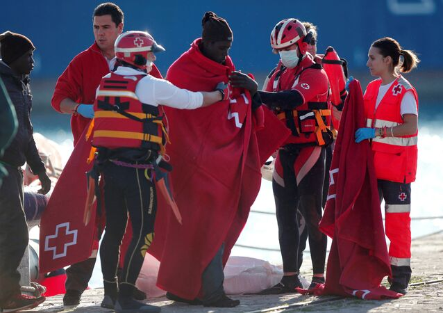 Migrants, who are part of a group intercepted aboard a dinghy off the coast in the Mediterranean sea, are assisted by members of Spanish Red Cross after arriving on a rescue boat at a port in Malaga, southern Spain, January 1, 2017