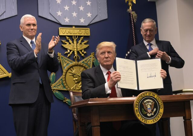 US President Donald Trump shows his signature on executive orders alongside US Defense Secretary James Mattis and US Vice President Mike Pence on January 27, 2017, at the Pentagon in Washington, DC