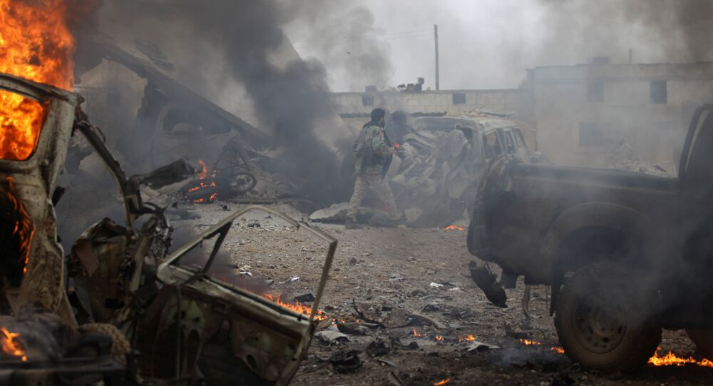 A rebel fighter walks near damaged vehicles after a car bomb explosion in Jub al Barazi east of the northern Syrian town of al-Bab, Syria January 15, 2017
