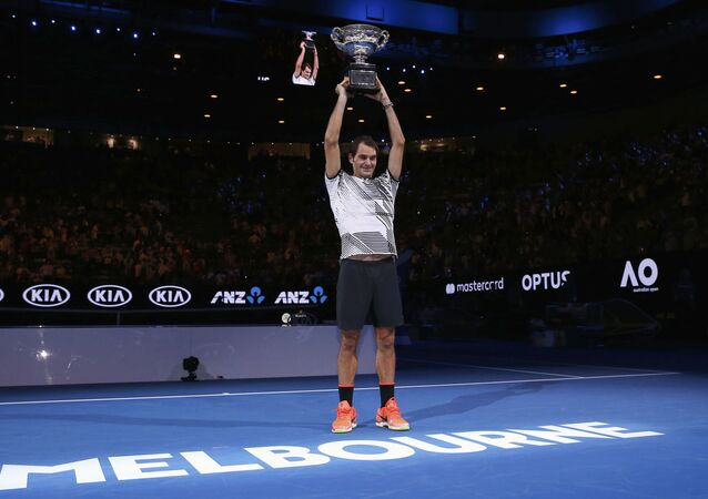 Switzerland's Roger Federer holds up the trophy after winning his Men's singles final match against Spain's Rafael Nadal