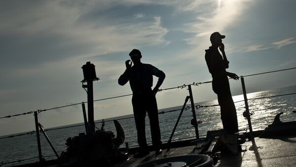 Royal Malaysian Navy personnel are silhoutted as they stand aboard a naval ship during a search and rescue mission for boat-people, near the Thai-Malaysia border north of Langkawi island on May 28, 2015 - Sputnik International