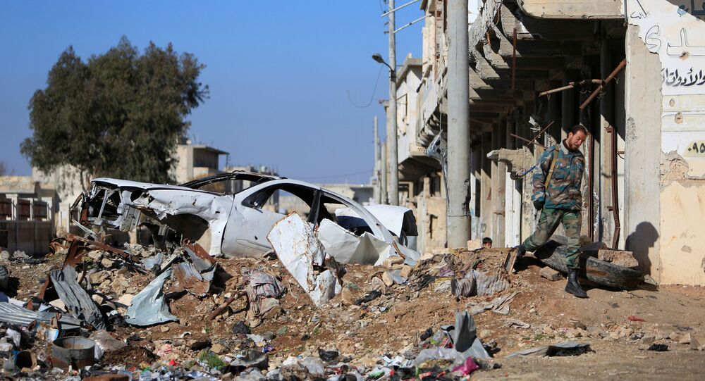 A Syrian government soldier walks near a damaged car on a road to Aleppo, Syria January 29, 2017