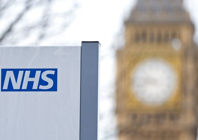 An NHS sign is pictured at St Thomas' Hospital in front of the Big Ben clock face and the Elizabeth Tower on January 13, 2017 in London.