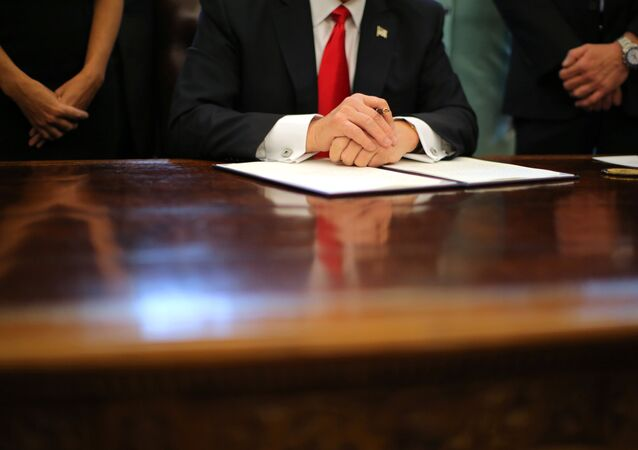 US President Donald Trump prepares to sign an executive order cutting regulations, accompanied by small business leaders at the Oval Office of the White House in Washington US, January 30, 2017.